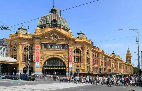 Facade of Flinders Street Station, Melbourne with lots of people crossing the road to and from the train station.