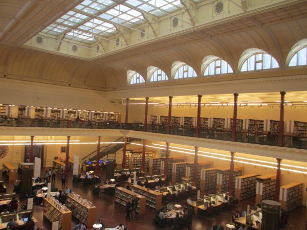 The Reading Room, State Library in Melbourne. A room with hundreds of bookshelves with books.