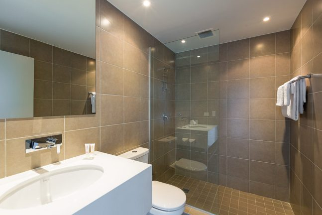 Miranda Metro Hotel Bathroom With Brown Tiles And Glass Shower Screen