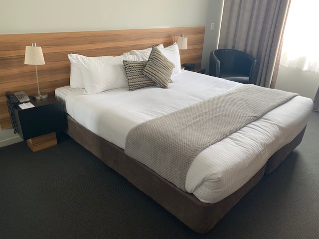 Miranda Metro Hotel Queen Size Bed With White Linen and Fawn Pillows And Throw