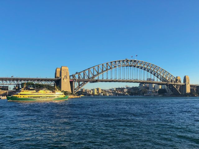 Sydney Harbour With The Metal Sydney Harbour Bridge With A Green And Gold Ferry Sailing In The Harbour.