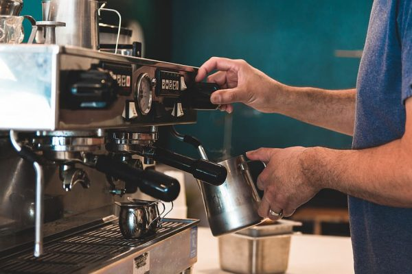 Person Making Coffee On A Commercial Coffee Maker.
