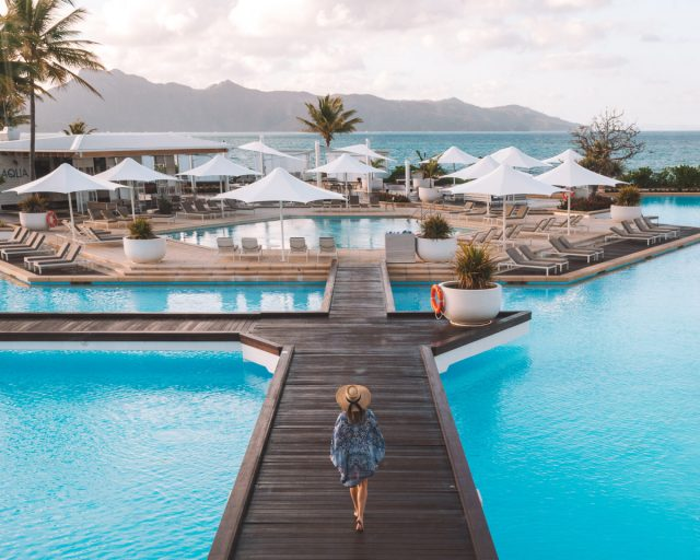 Hayman Island Resort Is An Island Resort Surrounded By Ocean But Has Pools With Many Lounge Chairs And Umbrella To Shade Yourself From The Sun.