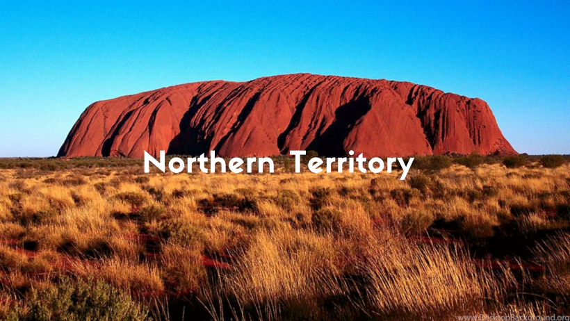 Uluru Or Ayers Rock On A Bright Sunny Day With Blue Sky And Rock Is A Beautiful Red Surrounded By Desert Weed In The Northern Territory.